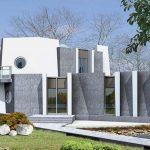 Casa de forma irregular con ventanas circulares
